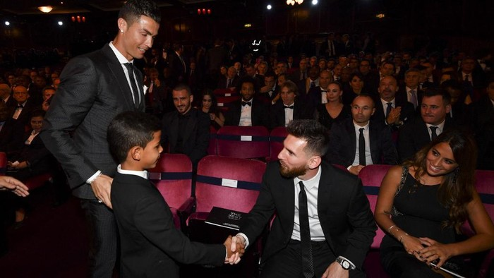 Nominee for the Best FIFA football player, Barcelona and Argentina forward Lionel Messi (2nd R) shakes hands with Cristiano Ronaldo Jr, son of Real Madrid and Portugal forward Cristiano Ronaldo (L) before The Best FIFA Football Awards ceremony, on October 23, 2017 in London. (Photo by Ben STANSALL / AFP)