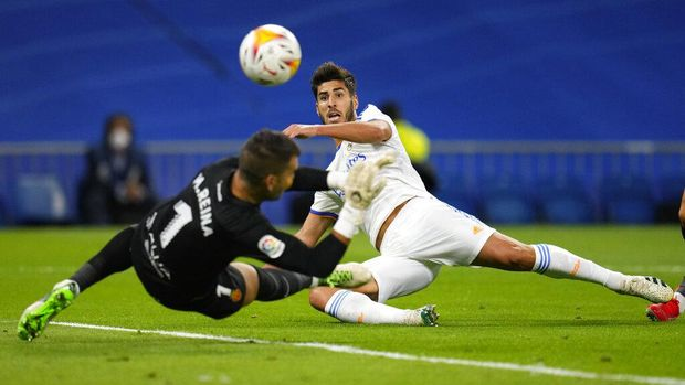 Real Madrid's Marco Asensio kicks the ball past Mallorca's goalkeeper Manolo Reina to score his team's third goal during a Spanish La Liga soccer match between Real Madrid and Mallorca at the Bernabeu stadium in Madrid, Spain, Wednesday, Sept. 22, 2021. (AP Photo/Manu Fernandez)