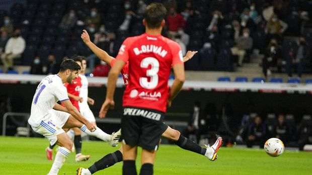 Real Madrid's Marco Asensio, left, scores his team's fourth goal during a Spanish La Liga soccer match between Real Madrid and Mallorca at the Bernabeu stadium in Madrid, Spain, Wednesday, Sept. 22, 2021. (AP Photo/Manu Fernandez)