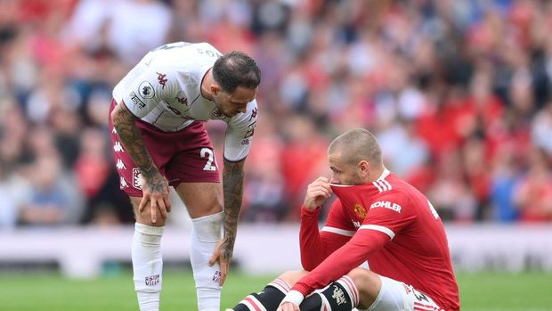 MANCHESTER, ENGLAND - SEPTEMBER 25: An injured Luke Shaw of Manchester United is checked on by Matty Cash of Aston Villa during the Premier League match between Manchester United and Aston Villa at Old Trafford on September 25, 2021 in Manchester, England. (Photo by Laurence Griffiths/Getty Images)