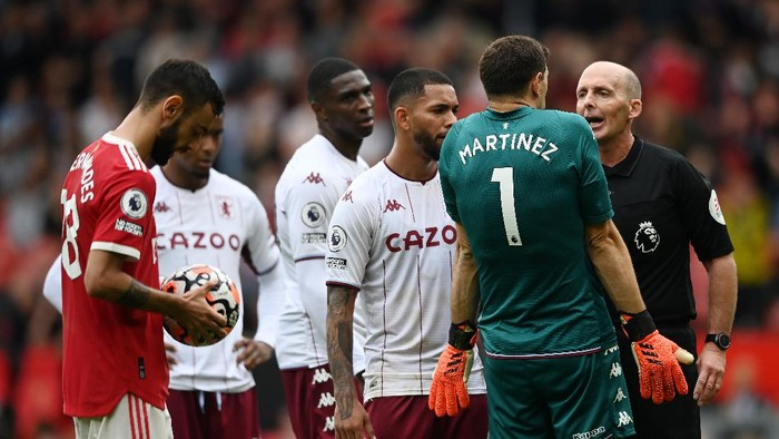 MANCHESTER, ENGLAND - SEPTEMBER 25: Referee Mike Dean speaks to Emiliano Martinez of Aston Villa  during the Premier League match between Manchester United and Aston Villa at Old Trafford on September 25, 2021 in Manchester, England. (Photo by Gareth Copley/Getty Images)