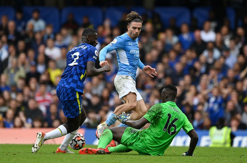 LONDON, ENGLAND - SEPTEMBER 25: Jack Grealish of Manchester City is challenged by Antonio Ruediger and Edouard Mendy of Chelsea during the Premier League match between Chelsea and Manchester City at Stamford Bridge on September 25, 2021 in London, England. (Photo by Shaun Botterill/Getty Images)
