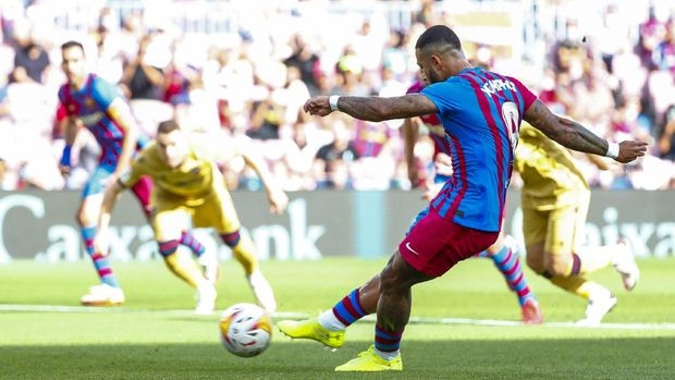 Barcelona's Memphis Depay scores from a penalty kick during a Spanish La Liga soccer match between FC Barcelona and Levante at the Camp Nou stadium in Barcelona, Spain, Sunday, Sept. 26, 2021. (AP Photo/Joan Monfort)