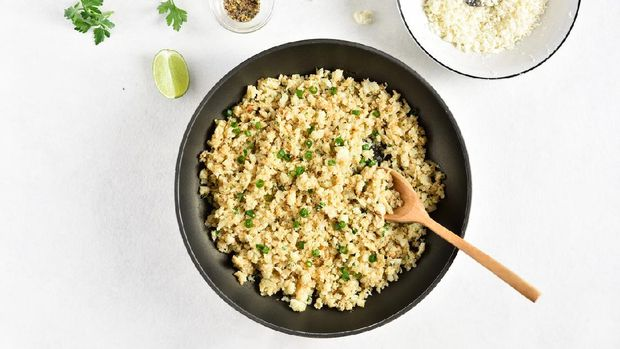 Roasted cauliflower rice on light stone background with free text space. Top view, flat lay