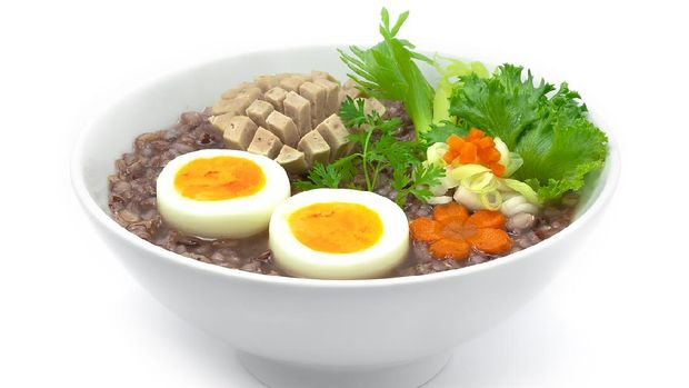 Rice Porridge Served Boiled Egg and Vietnames Saucesage decorate with carved carrots and vegetable sideview