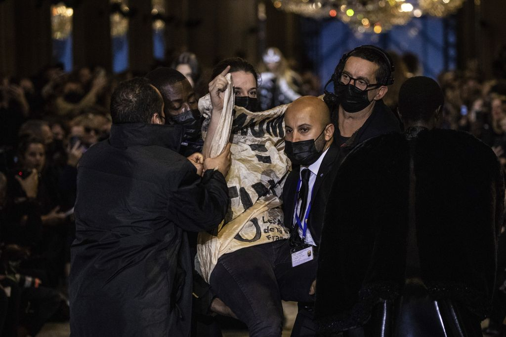 A protestor is removed from the runway during the Louis Vuitton Spring-Summer 2022 ready-to-wear fashion show presented in Paris, Tuesday, Oct. 5, 2021. (Photo by Vianney Le Caer/Invision/AP)