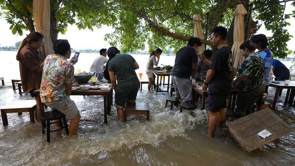 Tak sedikit pengunjung yang mengabadikan momen mereka makan di tengah banjir lewat ponsel masing-masing.