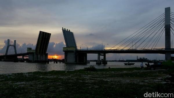 Saat matahari terbenam adalah waktu yang tepat untuk menikmati keindahan senja di balik Jembatan Emas tersebut. Terlebih saat jembatan itu mengangkat dan tertutup.
