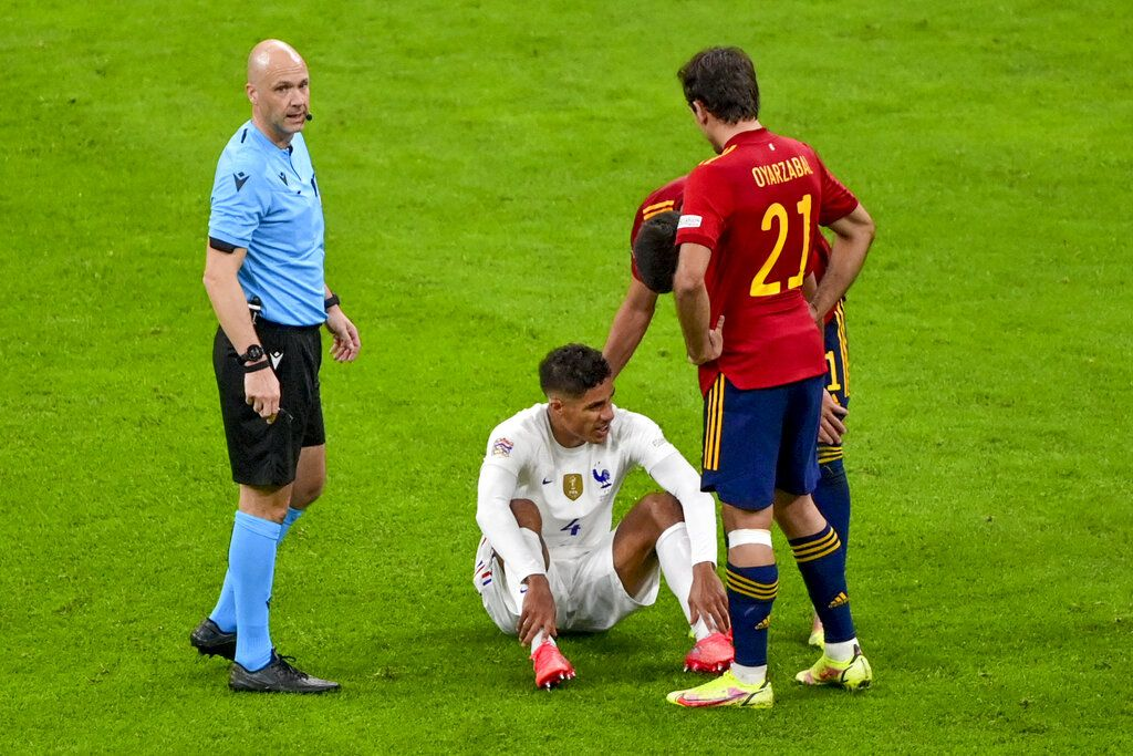 France's Raphael Varane sits on the pitch after an injury during the UEFA Nations League final soccer match between Spain and France at the San Siro stadium, in Milan, Italy, Sunday, Oct. 10, 2021. (Miguel Medina/Pool Photo via AP)