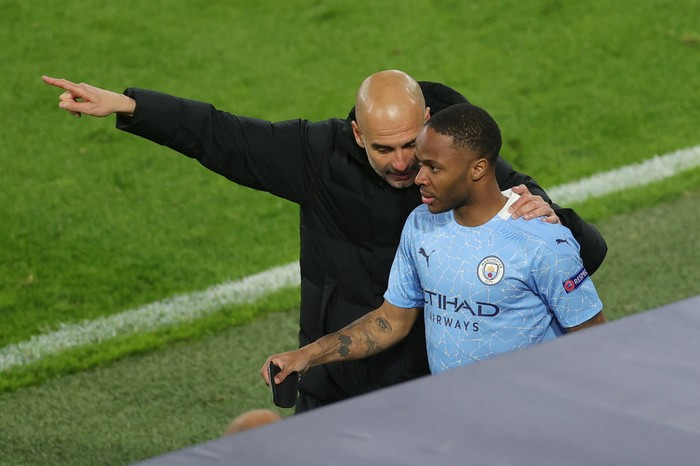 DORTMUND, GERMANY - APRIL 14: Pep Guardiola, Manager of Manchester City speaks with Substitute, Raheem Sterling of Manchester City during the UEFA Champions League Quarter Final Second Leg match between Borussia Dortmund and Manchester City at Signal Iduna Park on April 14, 2021 in Dortmund, Germany. Sporting stadiums around Germany remain under strict restrictions due to the Coronavirus Pandemic as Government social distancing laws prohibit fans inside venues resulting in games being played behind closed doors.  (Photo by Friedemann Vogel - Pool/Getty Images)