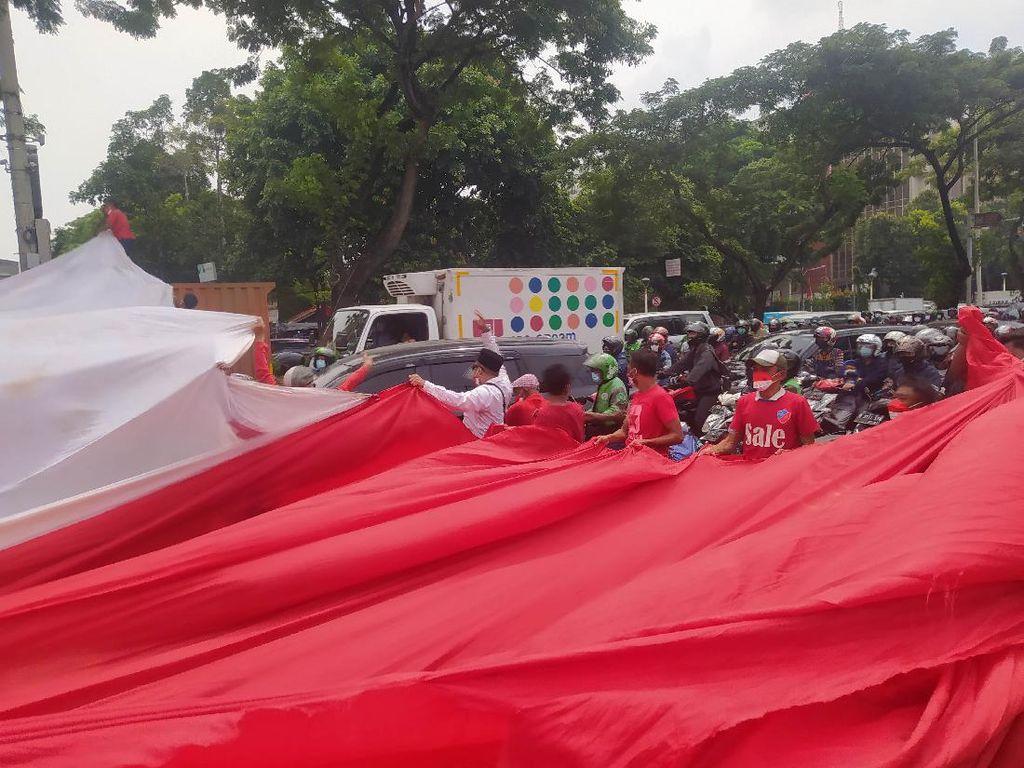 Buruh Bentangkan Bendera Merah Putih Raksasa Depan Museum Sumpah Pemuda