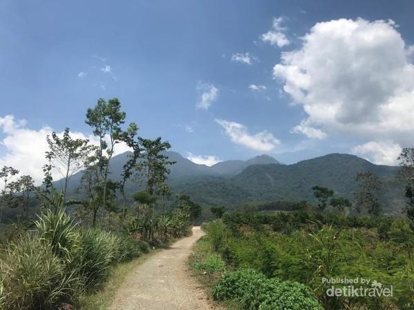 Akses jalan beton mendekati Coban. Terlihat Gunung Kawi di latar belakang.