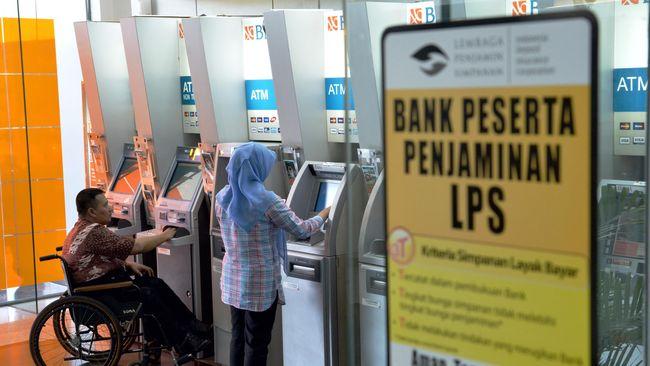 Dua nasabah melakukan transaksi dengan mesin ATM yang tak jauh dari stiker Lembaga Penjaminan Simpanan (LPS), di Bank Negara Indonesia (BNI) 46 Kantor Cabang Utama Graha Pangeran Surabaya, Jumat (24/10). LPS memiliki ruang untuk menurunkan suku bunga penjaminan (LPS Rate) sebesar 25 basis poin (bps) hingga 50 bps, yang merupakan langkah lanjutan terhadap penurunan tingkat suku bunga di pasar. ANTARA FOTO/Eric Ireng/ed/nz/14