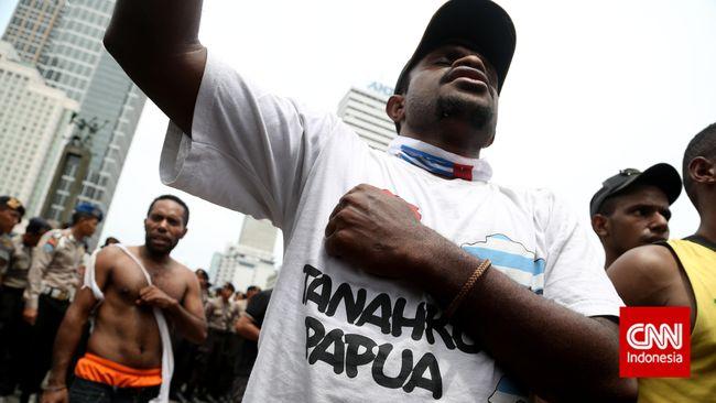 Sejumlah mahasiswa Papua yang tergabung dalam Aliansi Mahasiswa Papua (AMP) menyanyi saat berunjuk rasa di kawasan Bundaran HI, Jakarta, Senin, 1 Desember 2014. Mereka meminta Indonesia memberikan kebebasan dan hak menentukan nasib sendiri sebagai solusi demokratis bagi rakyat Papua Barat dan menarik militer organik dan non-organik dari seluruh tanah Papua. CNN Indonesia/Safir Makki