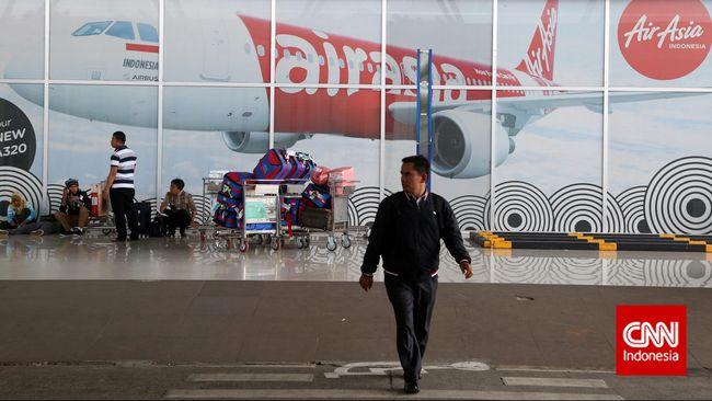 Pengunjung berlalu lalang di depan poster besar pesawat Air Asia di Terminal 3 Bandara Soekrarno Hatta, Banten, Tangerang, Minggu, 28 Desember 2014. CNN Indonesia/Safir Makki