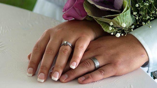 Pasangan pengantin mengenakan pakaian selam yang dimodifikasi seperti busana pesta. Mereka juga dibekali dengan peralatan menyelam.