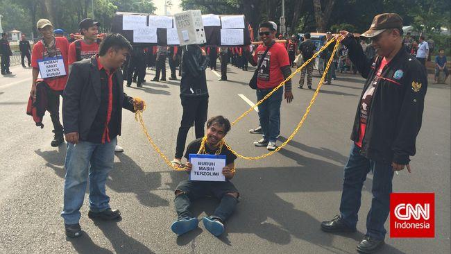 Massa berasal dari Serikat Buruh Sejahtera Indonesia yang melakukan aksi long march dari area timur Monas menuju Istana Negara.