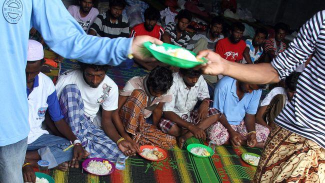 Berbulan-bulan terkatung-katung di laut, pengungsi Rohingya menangis ketika diberikan makanan ketika mereka sampai di daratan Aceh.