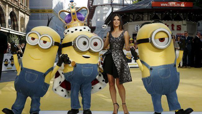 Di film Minions, Sandra Bullock dikerubuti tiga makhluk kuning imut. Di dunia nyata, sang aktris cantik diburu banyak bujangan Inggris.