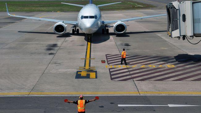 Petugas mengarahkan pesawat komersil untuk parkir di Bandara Adi Soemarmo, Boyolali, Jawa Tengah, Selasa (30/6).  PT. Angkasa Pura I, Bandara Adi Soemarmo berencana akan menambahkan jadwal penerbangan dari biasanya hanya 2100 menjadi 3000 jadwal penerbangan untuk mengantisipasi extra flight mudik lebaran 2015. ANTARA FOTO/ Aloysius Jarot Nugroho/ss/foc/15.