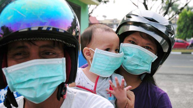 Sejumlah warga mengenakan masker medis yang dibagiakan Dinas Kesehatan Provinsi Riau saat kabut asap kebakaran menyelimuti Kota Pekanbaru, Senin (27/7). Dinas Kesehatan Riau membagikan 1.000 masker karena kualitas udara terus menurun akibat polusi asap kebakaran hutan dan lahan, serta meminta warga mengurangi aktivitas di luar ruangan. ANTARA FOTO/FB Anggoro/Rei/pd/15.
