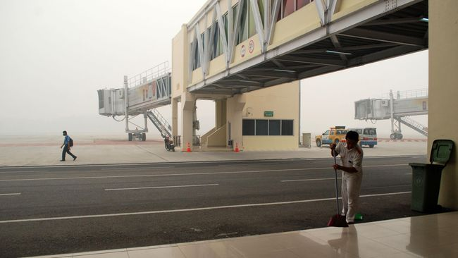 Petugas membersihkan area landasan pacu yang tidak beroperasi karena diselimuti kabut asap di Bandara Sultan Syarif Kasim II, di Pekanbaru, Riau, Senin (14/9). Kabut asap kebakaran hutan dan lahan yang menyelimuti landasan pacu bandara mengakibatkan 12 penerbangan menuju dan dari Pekanbaru dibatalkan. ANTARA FOTO/Rony Muharrman/kye/15