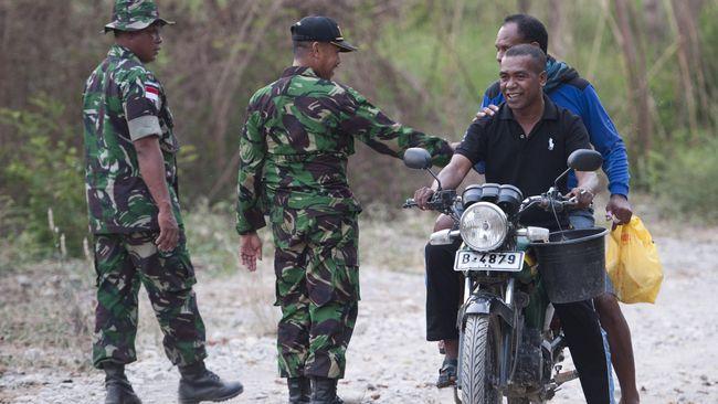 Anggota Satuan Tugas Pengamanan Perbatasan (Satgas Pamtas) RI-Timor Leste berbicang dengan warga Timor Leste di daerah perbatasan Tanubibi, Timor Leste.