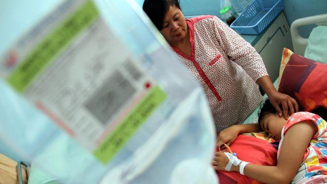 Seorang ibu menunggui putrinya yang menjalani perawatan akibat penyakit demam berdarah (DB) di ruang instalasi rawat inap RSUD dr Iskak, Tulungagung, Jawa Timur, Jumat (15/1). Dinas kesehatan setempat memberlakukan status Siaga 1 demam berdarah menyusul meninggalnya seorang pasien anak penderita DB dan meningkatnya jumlah penderita akibat penyakit tersebut. ANTARA FOTO/Destyan Sujarwoko/aww/16