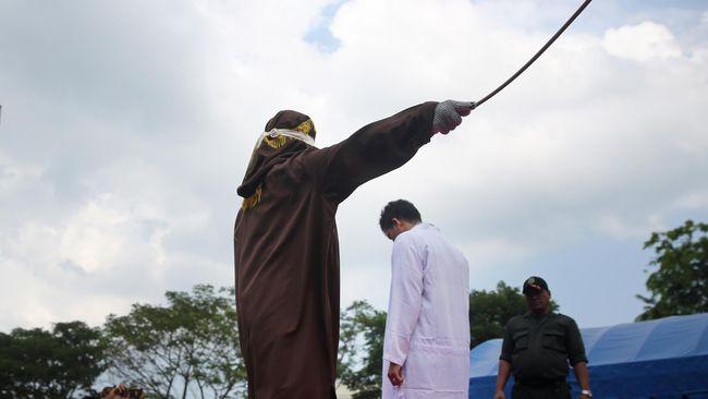 Terpidana pelanggar peraturan daerah (qanun) Syariat Islam (tengah) menjalani hukuman cambuk di halaman Masjid Rukoh, Kecamatan Syiah Kuala, Banda Aceh, Aceh, Selasa (1/3). Mahkamah Syar'iah Kota Banda Aceh menjatuhkan hukuman antara enam hingga 40 kali cambuk terhadap 18 warga yang tertangkap tangan bermain judi (maisir), minuman keras (khamar) dan mesum (khalwat) sesuai qanun Nomor 6/2014 tentang hukum jinayat. ANTARA FOTO/Irwansyah Putra/Spt/16.