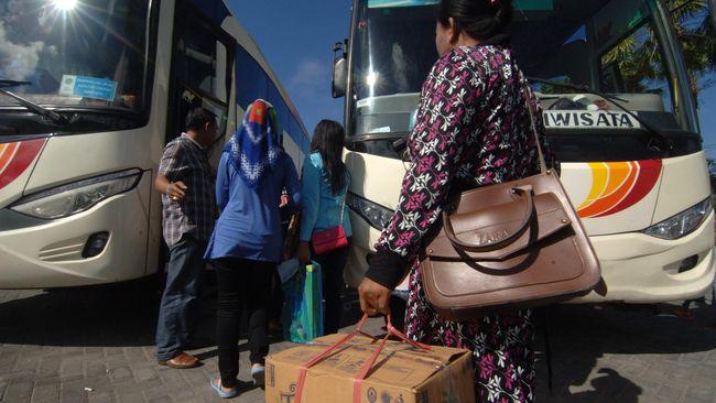 Sejumlah warga bersiap naik ke atas bus saat mudik gratis di Pamekasan, Jawa Timur, Jumat (9/7). Mudik bersama gratis itu difasilitasi Dishub Jatim bekerjasama dengan Pemkab Pamekasan untuk memberikan kemudahan bagi warga untuk kembali ke perantauan. ANTARA FOTO/Saiful Bahri/foc/16.