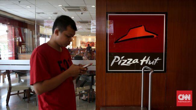 Pengunjung melintasi restaurant cepat saji Pizza Hut di Jakarta, Minggu, 4 September 2016. CNN Indonesia/Safir Makki