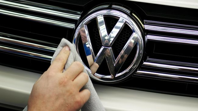 (FILES) This file photo taken on March 07, 2012 shows a Volkswagen worker polishing the logo on the front of a car coming off the assembly line for the VW Tiguan and Touran models in Wolfsburg, central Germany. One year after 'Dieselgate', Volkswagen (VW) faces lawsuits around the world. So far, VW has refused to compensate Europeans or buy back their vehicles -- as the firm has done for many US customers. Instead, it plans to retrofit the 8.5 million vehicles affected to meet emissions standards honestly. Experts predict that the total bill for Volkswagen could reach between 25 and 30 billion euros, leaving the firm once again raiding its piggy bank but not threatening its survival. / AFP PHOTO / ODD ANDERSEN