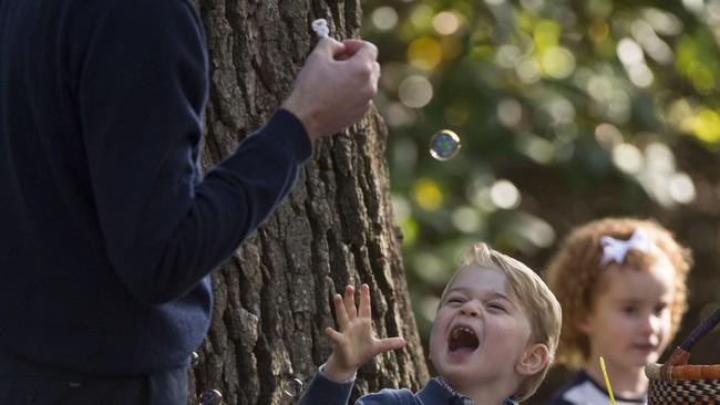 Menemani Pangeran George, Pangeran William pun tak malu-malu ikut bermain buih sabun dengan putra pertamanya itu. Di tempat lain, Putri Charlotte asyik bermain dengan balon-balon bersama Kate.(REUTERS/Chris Wattie)