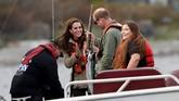 Pangeran William memegang ikan dan menunjukkan kepada Kate saat memancing terlihat pada saat berkunjung ke Haida Gwaii di Skidegate, British Columbia, Kanada. (REUTERS/Chris Wattie)