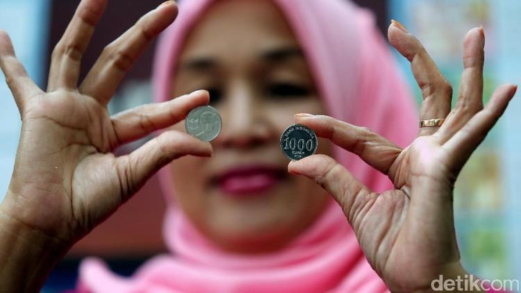 Usai antre untuk menukarkan uang, sejumlah warga memamerkan uang rupiah baru.