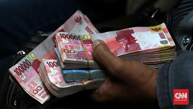 Nasabah memegang uang rupiah pecahan Rp 100 ribu di Jakarta, Senin, 19 Desember 2016. CNN Indonesia/Safir Makki