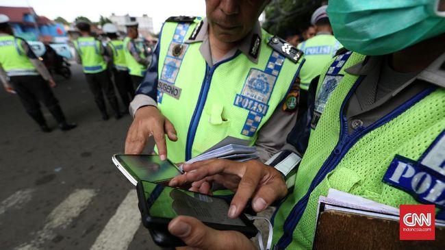 Petugas polantas menilang pengendara motor menggunakan aplikasi e-tilang saat razia kendaraan di kawasan Kampung Melayu, Jakarta, Rabu, 4 Januari 2017. Pemberlakuan e-tilang ini terintegrasi dengan pengadilan dan kejaksaan. Pengendara diwajibkan membayar denda maksimal sesuai pasal yang dilanggar. CNN Indonesia/Safir Makki