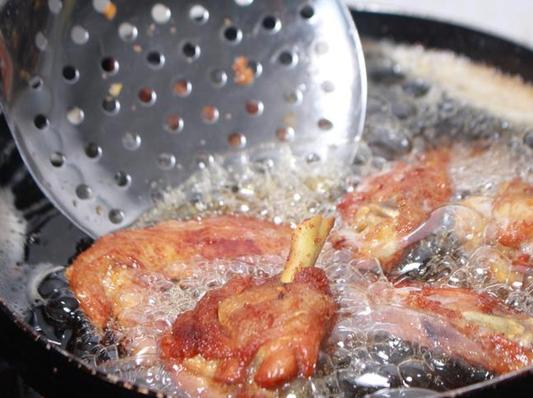 Close up image of cooking chicken in deep fry