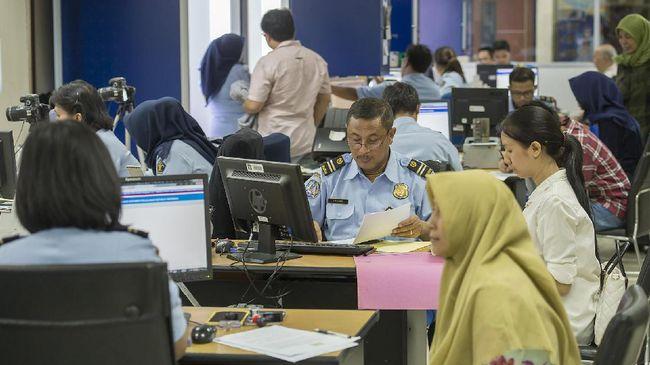 Petugas Kantor Imigrasi Kelas I Jakarta Pusat memberikan pelayanan pembuatan paspor di Kantor Imigrasi Kelas I Jakarta Pusat, Jakarta, Selasa (21/3). Kepala Kantor Imigrasi Kelas I Jakarta Pusat Tato Juliadin Hidayawan mengatakan pihaknya akan terus melakukan dan meningkatkan pemeriksaan secara cermat dan selektif terhadap kebenaran syarat formil dan materil yang dilampirkan dalam permohonan pembuatan paspor meskipun Ditjen Imigrasi Kemenkumham telah mencabut aturan soal nominal saldo tabungan sekurang-kurangnya Rp25 juta. ANTARA FOTO/Widodo S. Jusuf/foc/17.
