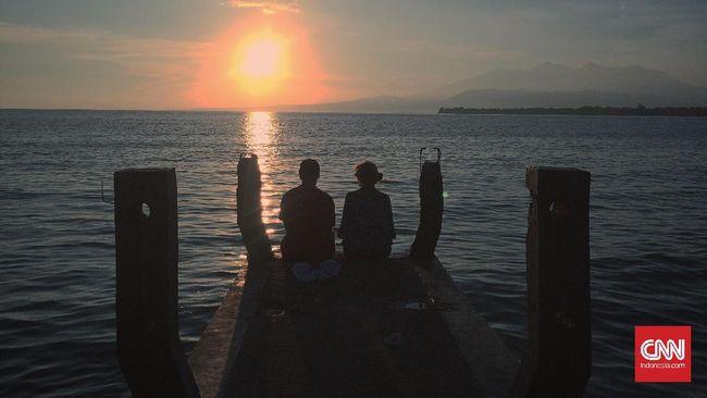 Sepasang wisatawan mancanegara yang tengah berbulan madu di Gili Meno tengah menikmati pemandangan matahari terbit di Jetty Bar.
