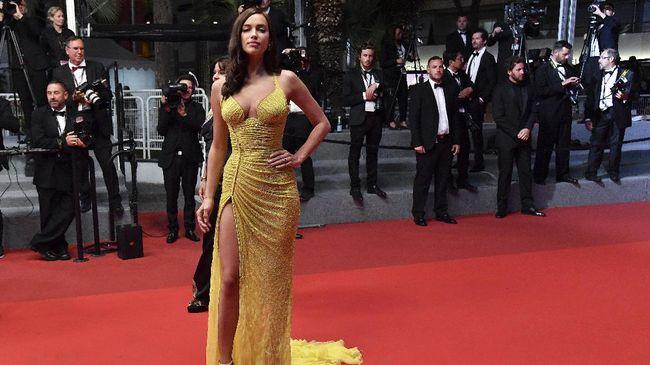 Berjalan di karpet merah Festival Film Cannes 2017, model yang baru melahirkan Maret lalu ini pamer tubuh ramping dalam busana kuning yang mencolok mata.