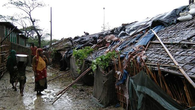 Rohingya refugees walk next to huts in a makeshift camp in Bangladesh's Cox's Bazar district on May 30, 2017 after Cyclone Mora made landfall in the region. Cyclone Mora hit Bangladesh on May 30, packing winds of up to 135 kilometres (84 miles) per hour, damaging thousands of homes as more than 300,000 people fled villages in the coastal district of Cox's Bazar, which bore the brunt of the cyclone. The district is home to 300,000 Rohingya refugees, most of whom live in flimsy makeshift camps after fleeing persecution in neighbouring Myanmar.  / AFP PHOTO / STR