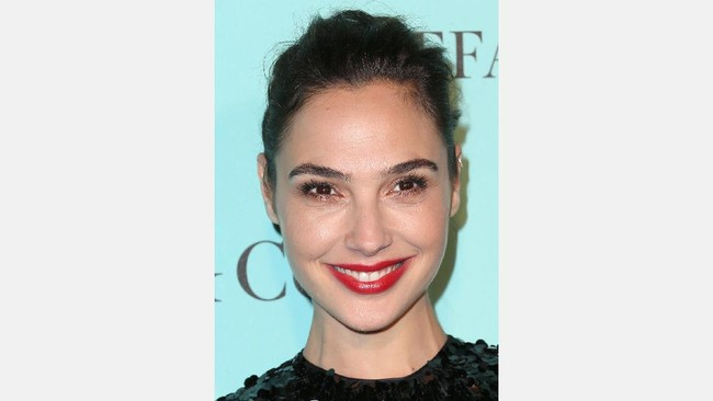 Lipstik dan gaun merah serta belahan dada rendah jadi sihir Gal Gadot setiap kali ia berjalan di karpet merah berbagai acara.