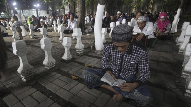 Umat muslim membaca Alquran di kawasan Makam Sunan Ampel, Surabaya, Jawa Timur, Kamis (15/6). Pada malam ke-21 Bulan Ramadan 1438 Hijriyah, kawasan Masjid dan Makam Sunan Ampel tersebut dikunjungi ribuan umat muslim untuk beribadah dan berharap mendapatkan malam Lailatulkadar yang diyakini sebagai malam yang lebih baik dari seribu bulan. ANTARA FOTO/Moch Asim/foc/17.