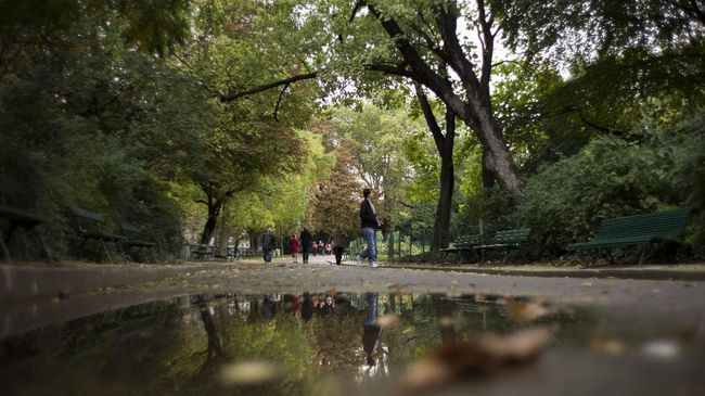 People walk in the Parc des Buttes Chaumont during the fall on October 11, 2012 in Paris. AFP PHOTO / FRED DUFOUR / AFP PHOTO / FRED DUFOUR