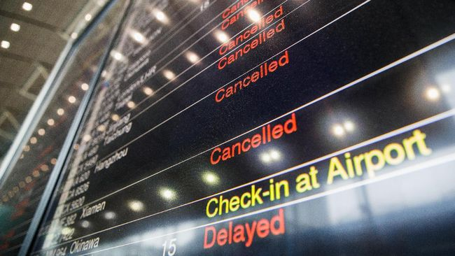 An information display showing lists of cancelled and delayed flights is seen at the Airport Express station as Typhoon Haima approaches Hong Kong on October 21, 2016, during a typhoon signal number eight warning.   The usually frenetic streets of Hong Kong were deserted on OCtober 21 as the city went into lockdown for Typhoon Haima, which has killed at least eight people in the Philippines. Flights were cancelled, roads were clear of cars and pavements empty, with schools and offices shut as the storm loomed southeast of Hong Kong.  / AFP PHOTO / Anthony WALLACE