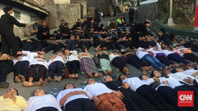 Puluhan warga masyarakat adat Sunda Wiwitan, Cigugur, Kuningan mulai berkumpul di depan jalan wilayah yang akan dieksekusi. Sebagian mereka terletang di jalan.