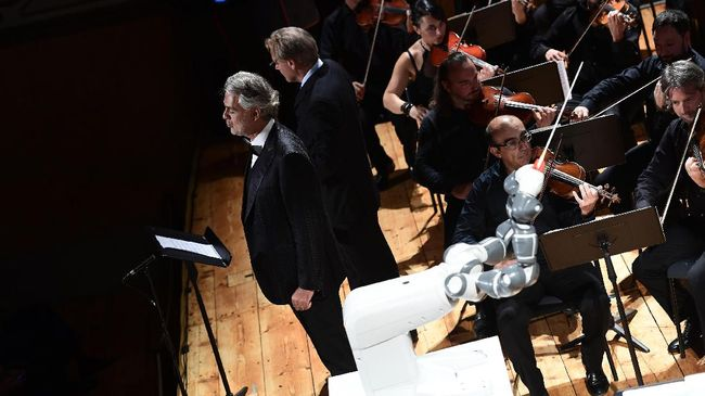 This photograph taken on September 12, 2017,  shows the robot 'Yumi' conducting Italian tenor Andrea Bocelli and The Lucca Philharmonic Orchestra in concert for the first time at The Teatro Verdi in Pisa. / AFP PHOTO / MIGUEL MEDINA