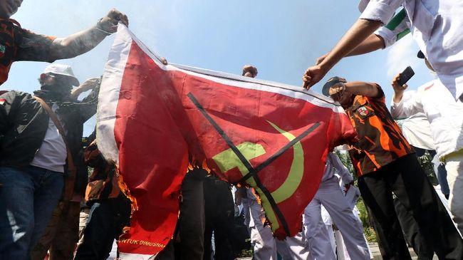 Sejumlah massa yang tergabung dalam Gerakan Rakyat Anti Komunis (Gertak) membakar spanduk saat berunjuk rasa di Taman Apsari, Surabaya, Jawa Timur, Sabtu (30/9). Aksi itu mengangkat tema 'Menolak Lupa Pengkhianatan G30S/PKI' dan menyerukan tentang bahaya laten Komunisme. ANTARA FOTO/Didik Suhartono/foc/17.