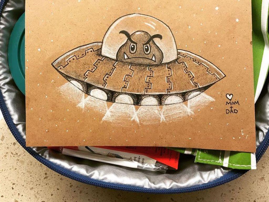 Gambar alien lengkap dengan ufo menghiasi selipan kertas di atas bekal makanan.